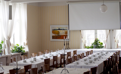 Kokouspöytä kahdessa rivissä sekä valkokangas Café Cabriolen kokoustilassa